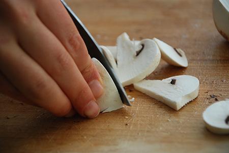 חיתוך פטריות שמפניון: קודם לחצי ואז לרצועות. אל תוותרו על הרגליים!